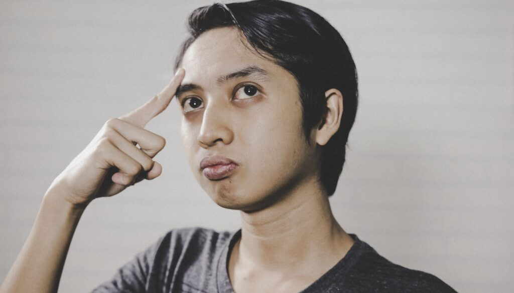 young man pointing to his head with his forefinger with a puzzled look on his face