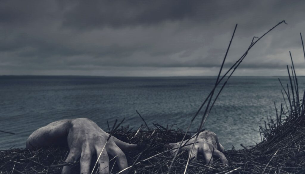 close up of a mans hands hanging on for dear life on a cliff with the ocean and sky in the background