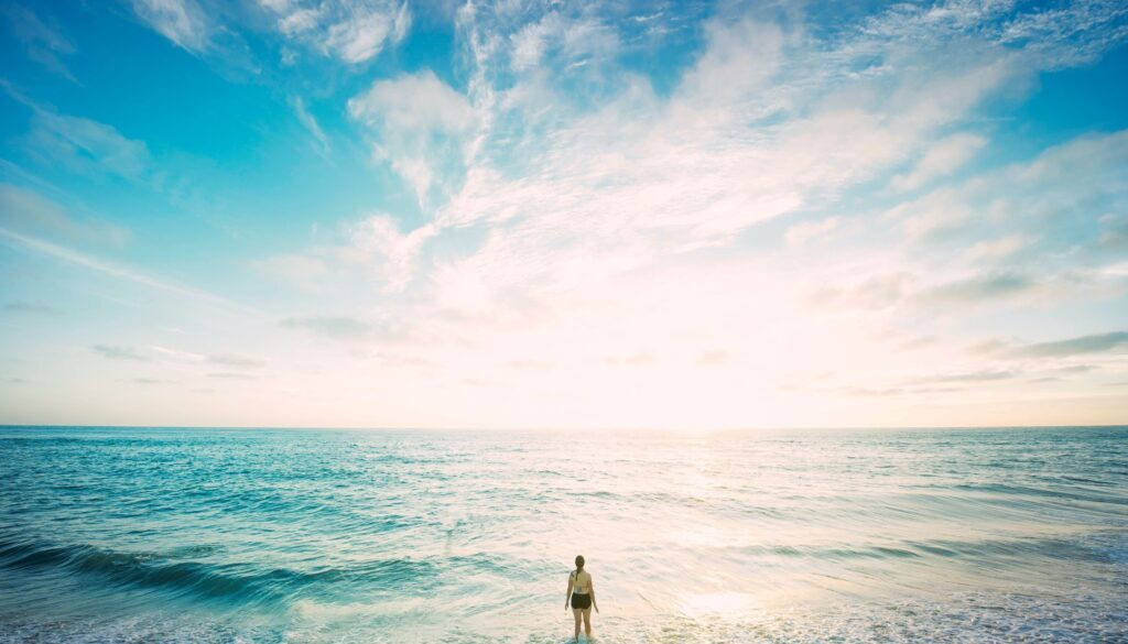 tiny woman standing at the edge of a huge ocean against a wide expanse of sky
