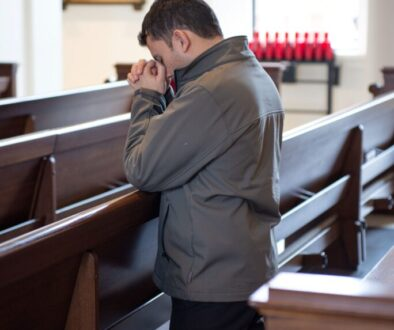 young man kneeling in prayer in an empty church