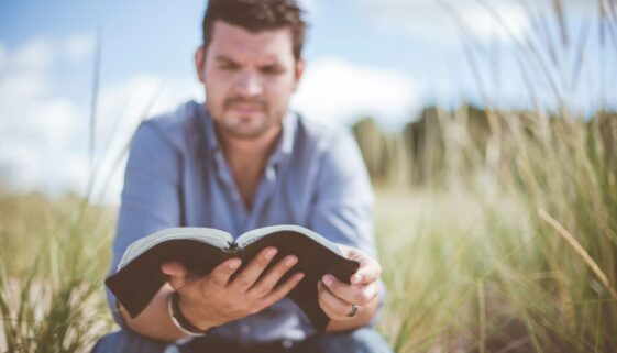 young man sitting in a field of grass reading his Bible