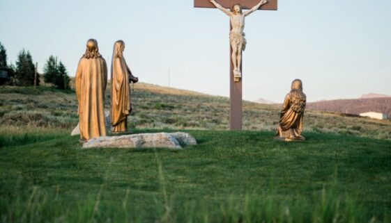 outdoor sculptures of Jesus on the Cross surrounded by wood sculptures of Mary, John, and others