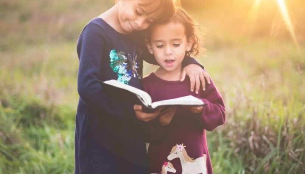 two little girls standing in a sunny field with arms entwined looking at an open Bible
